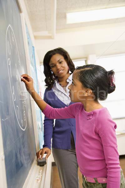 Nauczyciel student tablicy kobiet zegar rysunek Zdjęcia stock © iofoto