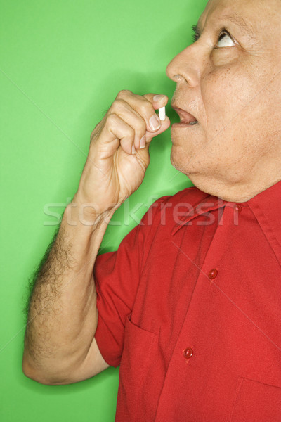 Man putting pill in mouth. Stock photo © iofoto