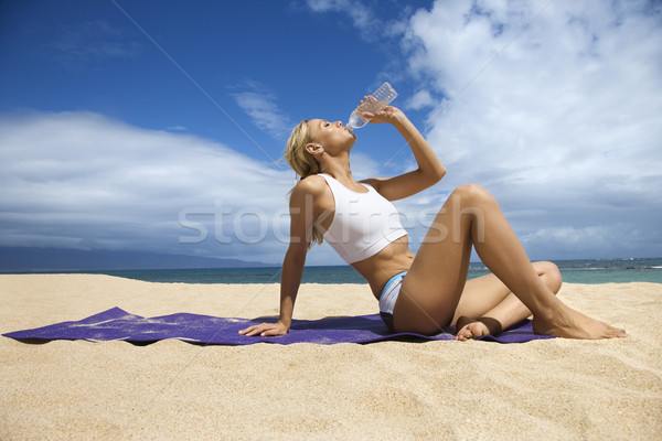 Attractive Young Woman Drinking on Beach Stock photo © iofoto