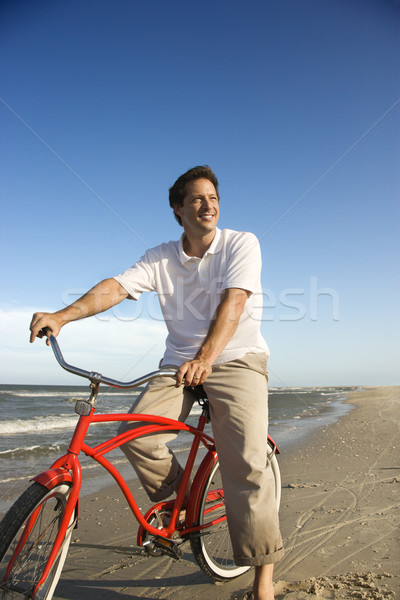 Man riding red bicycle on beach. Stock photo © iofoto
