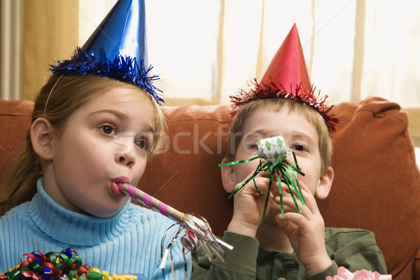 Children blowing noisemakers. Stock photo © iofoto
