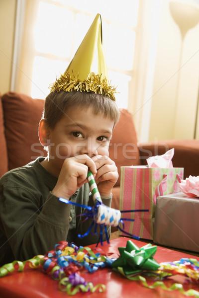 Boy blowing noisemaker. Stock photo © iofoto
