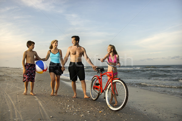 Stock photo: Family walking down the beach.