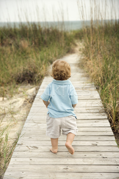 Little boy on beach walkway. Stock photo © iofoto