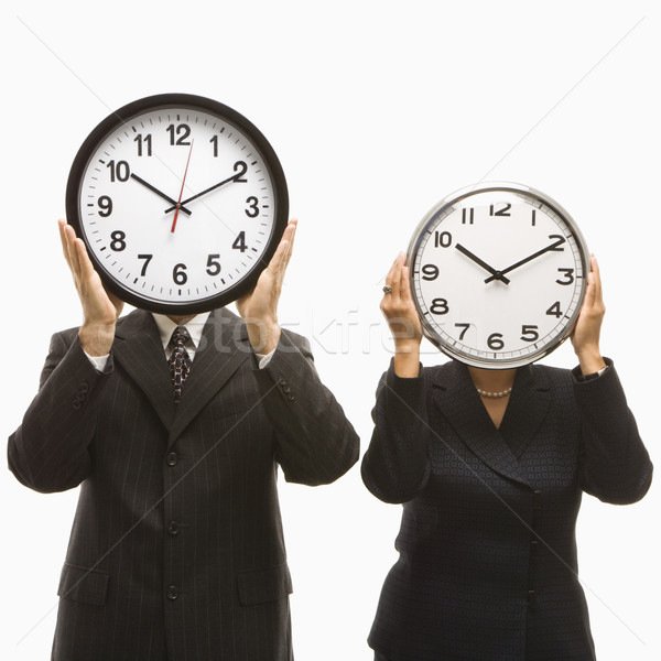 Stock photo: Businesspeople holding clocks.