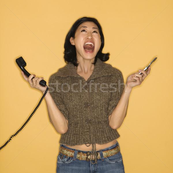 Woman holding telephones. Stock photo © iofoto