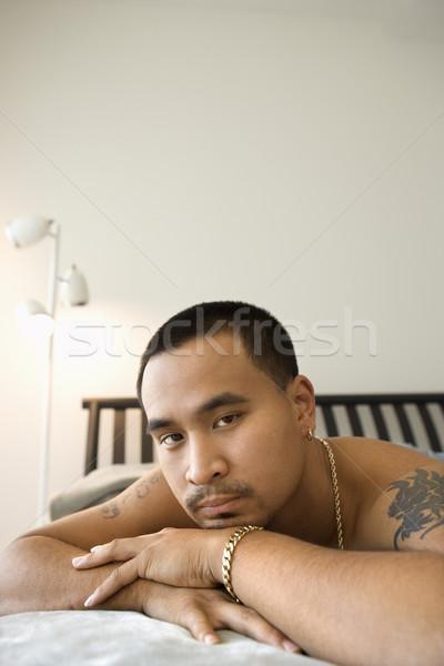 Człowiek bed półnagi asian Zdjęcia stock © iofoto