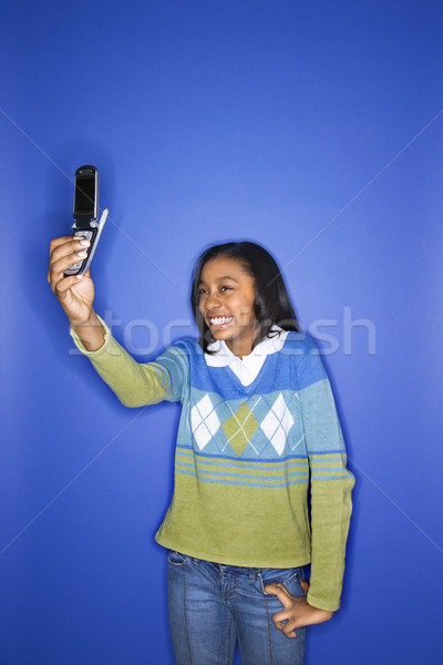 Girl using cellphone. Stock photo © iofoto