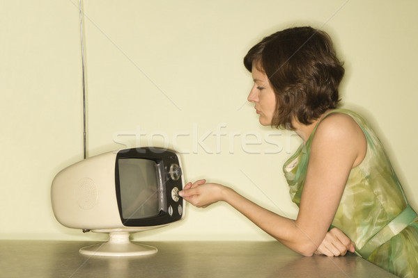 Stock photo: Woman dialing television.