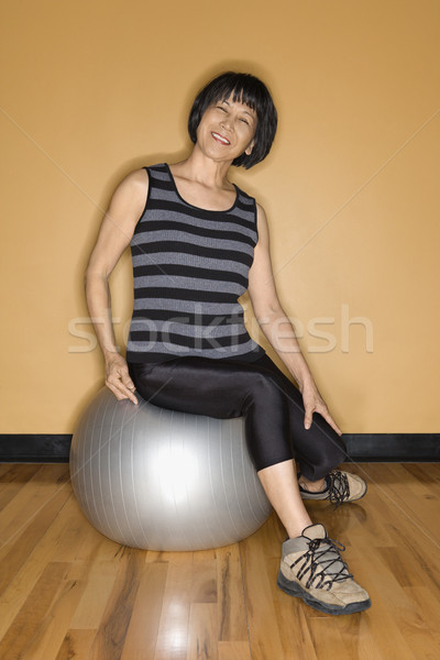 Idős nő ül egyensúlyozó labda mosolyog ázsiai Stock fotó © iofoto