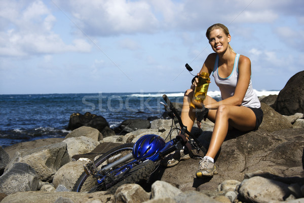 Attractive Young Woman Sitting With Bicycle on Rocky Beach Stock photo © iofoto