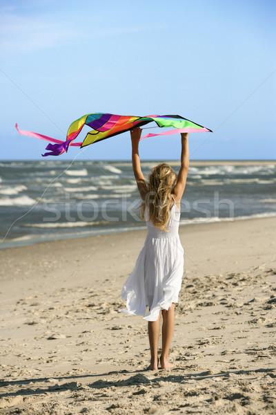 Girl holding kite on beach. Stock photo © iofoto
