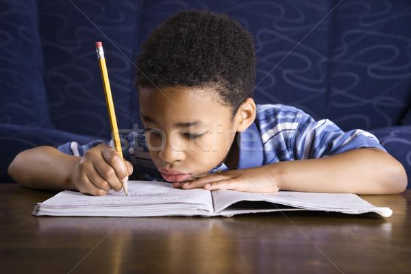 Chłopca praca domowa młodych posiedzenia piętrze Zdjęcia stock © iofoto
