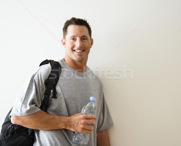 Férfi tornaterem táska áll mosolyog palackozott víz Stock fotó © iofoto