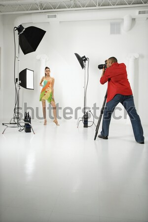 Stock photo: Young female model being photographed by male photographer.