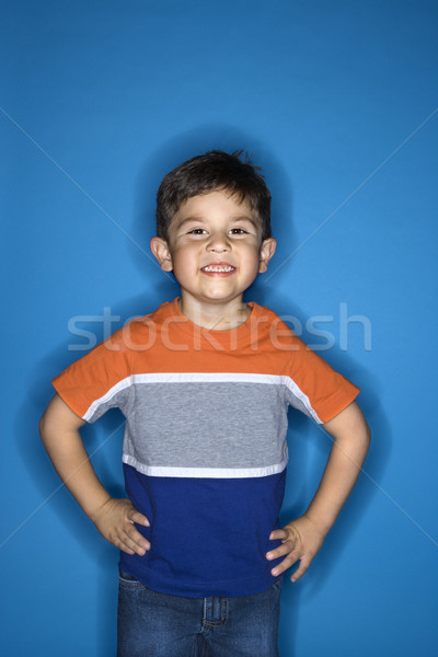 Boy standing with hands on hips. Stock photo © iofoto