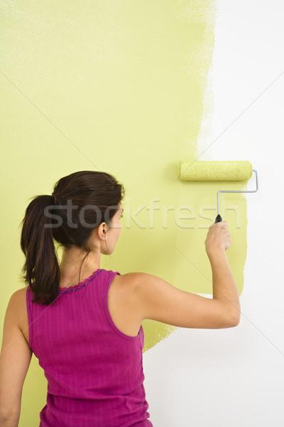 Stock photo: Woman painting wall.