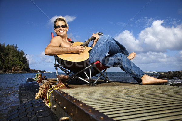 Genç oturma oynama gitar gömleksiz Stok fotoğraf © iofoto