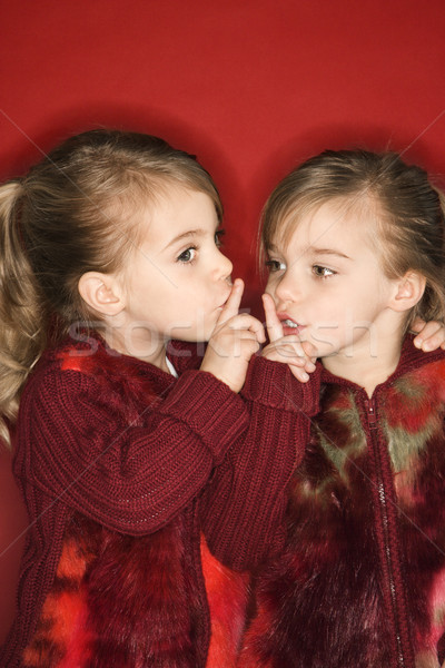 Twins holding fingers to mouths. Stock photo © iofoto