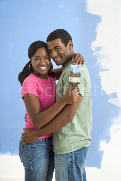 Happy couple next to half-painted wall. Stock photo © iofoto
