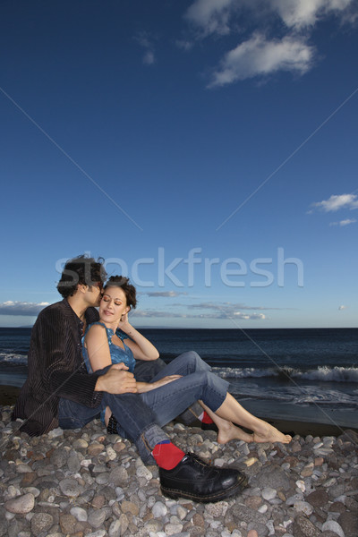 Couple snuggling on beach. Stock photo © iofoto