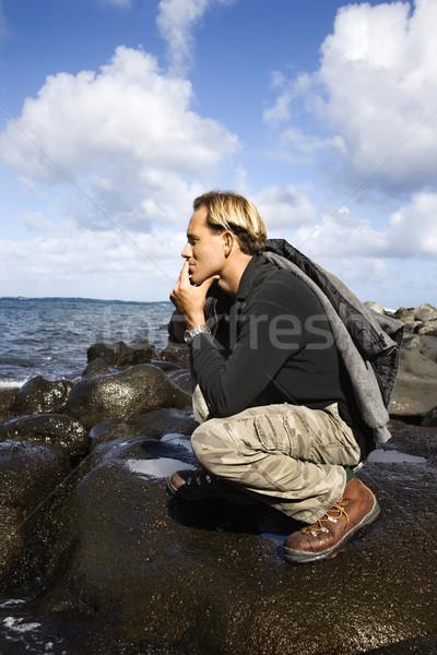Férfi térdel tengerpart part néz óceán Stock fotó © iofoto