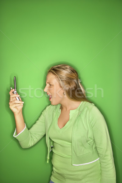 Girl looking shocked at cellphone. Stock photo © iofoto