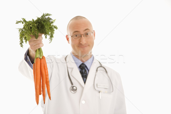 Doctor holding carrots. Stock photo © iofoto