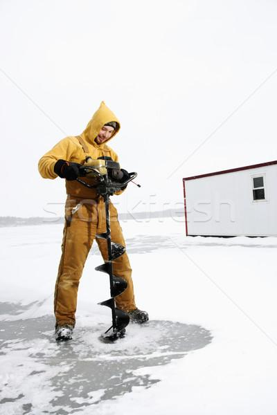 Férfi fúrás lyuk jég fiatalember citromsárga Stock fotó © iofoto