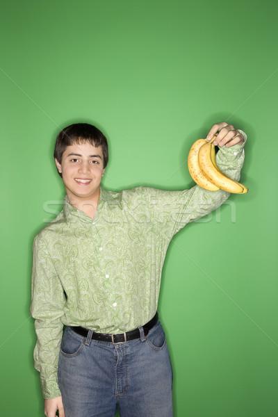 Teen boy holding bananas. Stock photo © iofoto