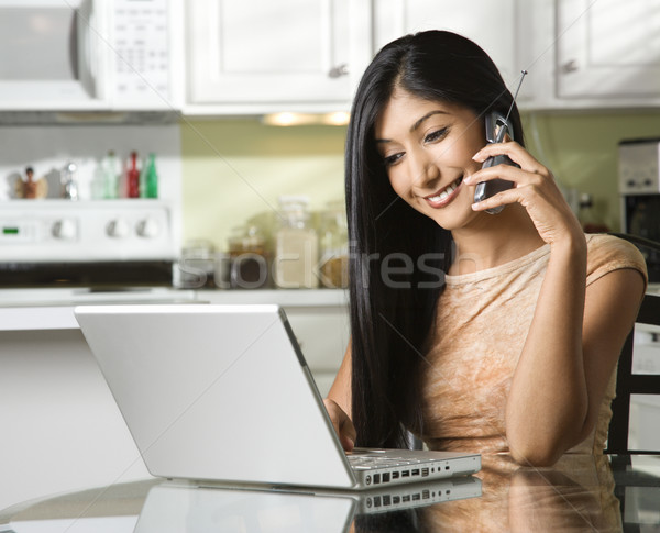 Young Woman Using Laptop and Talking on Cellphone Stock photo © iofoto
