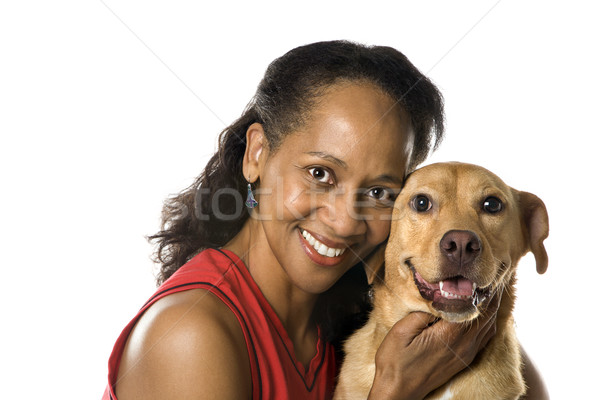 Woman holding dog and smiling. Stock photo © iofoto