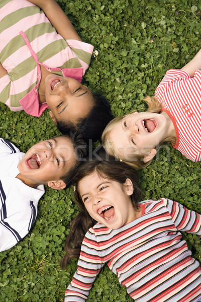 Children Lying in Clover Screaming With Heads Together Stock photo © iofoto