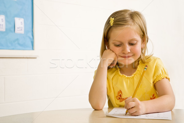 Young Girl Smiling in Classroom Writing on Paper Stock photo © iofoto