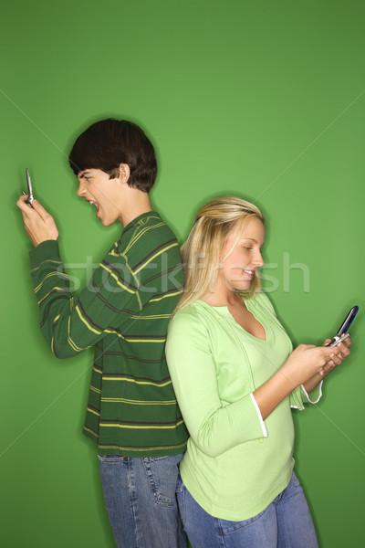 Boy and girl on cellphones. Stock photo © iofoto