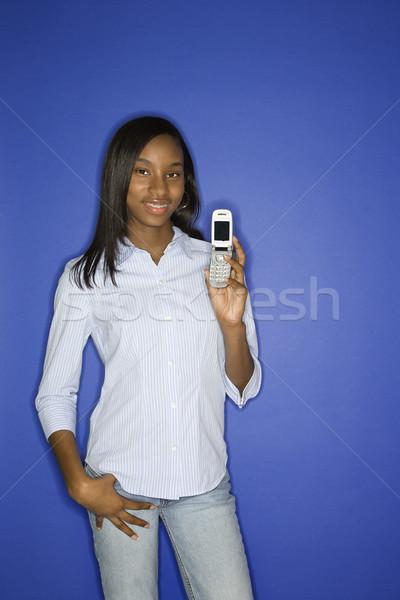 Teenage girl holding cellphone. Stock photo © iofoto
