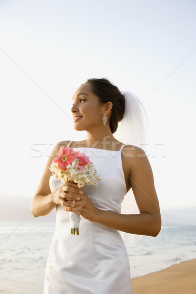 Bride holding bouquet on beach. Stock photo © iofoto