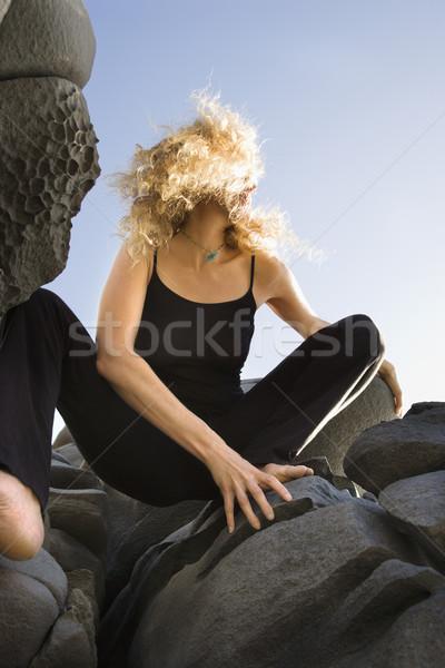 Woman crouching on rocks. Stock photo © iofoto