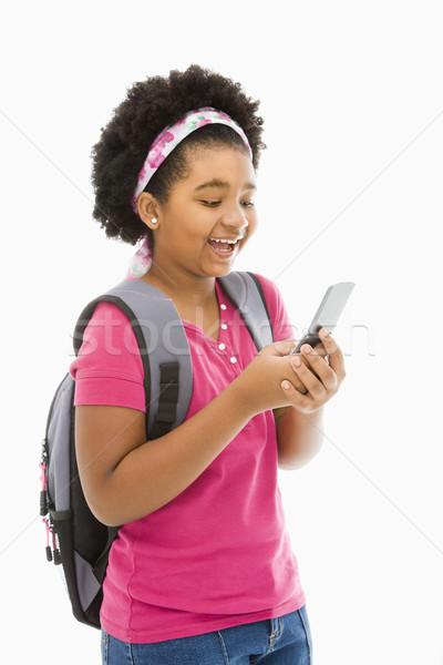Lány sms üzenetküldés afroamerikai hátizsák mobiltelefon könyv Stock fotó © iofoto