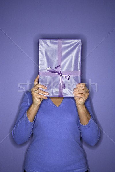 Woman hiding behind present. Stock photo © iofoto