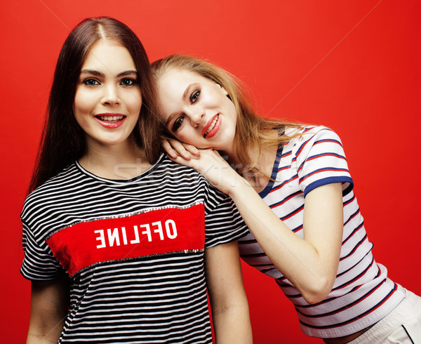 Stock photo: two best friends teenage girls together having fun, posing emotional on red background, besties happ