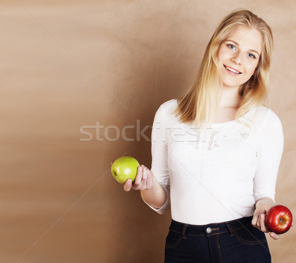 young pretty blond woman with green apple happy cheerful smiling close up on warm brown background,  Stock photo © iordani