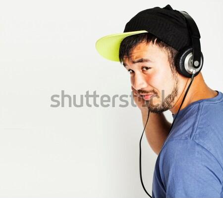 Jovem asiático homem seis fones de ouvido escuta Foto stock © iordani