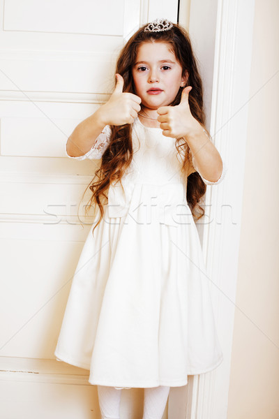 little cute girl at home, opening door well-dressed in white dre Stock photo © iordani