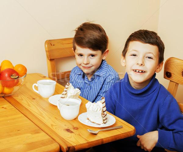 little cute boys eating dessert on wooden kitchen. home interior Stock photo © iordani