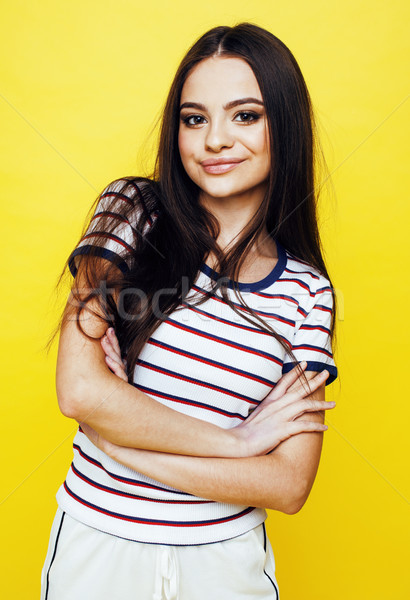 Stock photo: lifestyle people concept: pretty young school teenage girl having fun happy smiling on yellow backgr