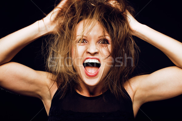 young silly crazy girl with messed hair making stupid faces on black background, lifestyle people co Stock photo © iordani