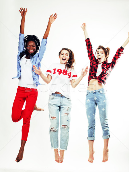 three pretty young diverse nations teenage girl friends jumping happy smiling on white background, l Stock photo © iordani