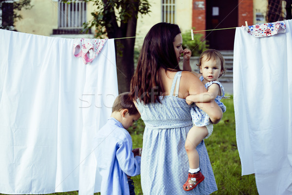 woman with children in garden hanging laundry outside, lifestyle people concept Stock photo © iordani