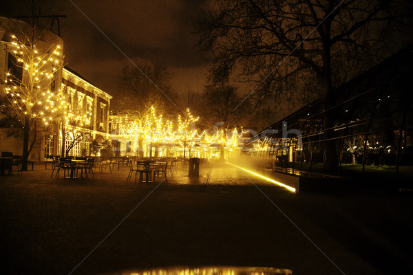 Stock photo: empty night restaurant, lot of tables and chairs with noone, magic fairy lights on trees like christ